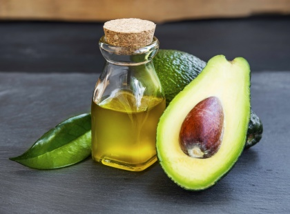 Avocado oil in bottle with avocado fruit